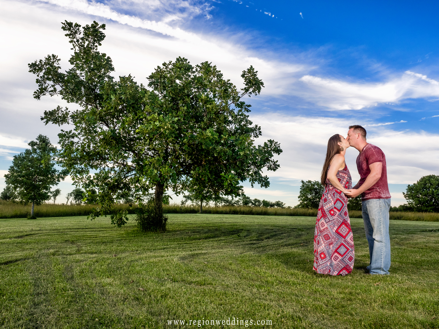 A couple shares a kiss next to a lone tree underneath blue skies.