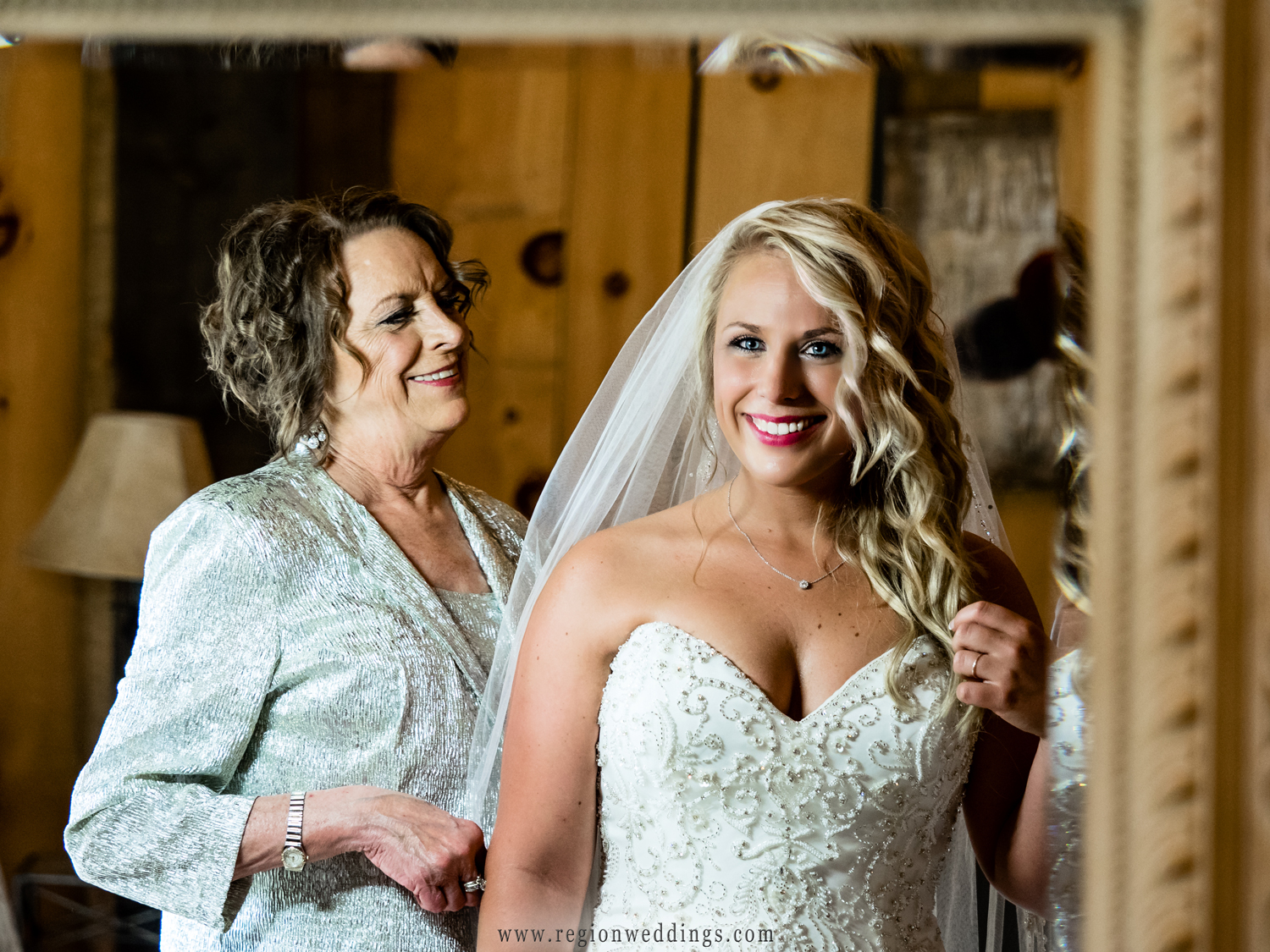 Mom helps her daughter on wedding day with her dress and veil.