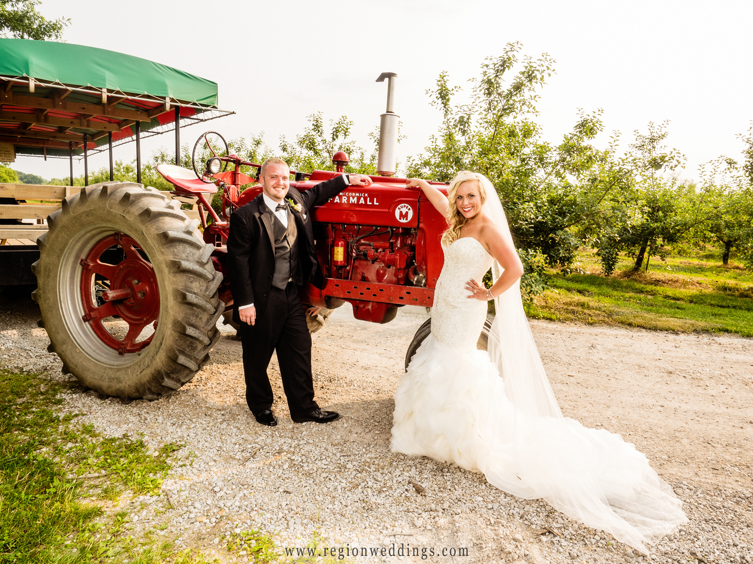 The bride and groom alongside a tractor at County Line Orchard.