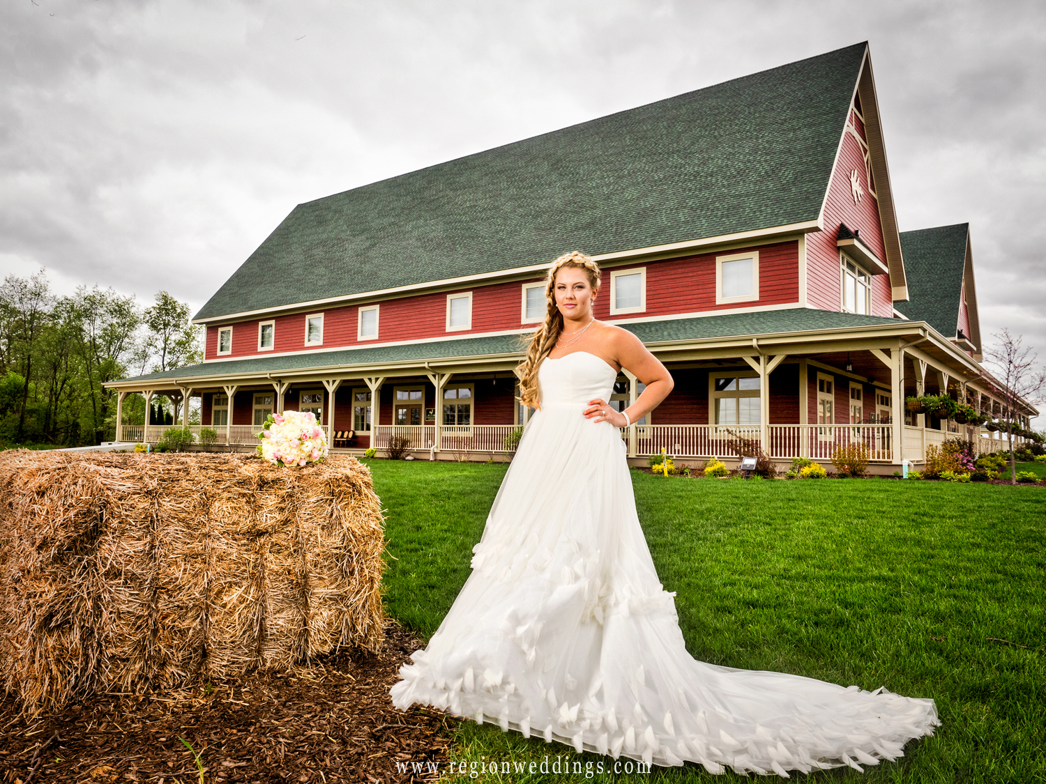 A bride in front of the Farmhouse Restaurant with her bouquet of flowers on a bale of hay.