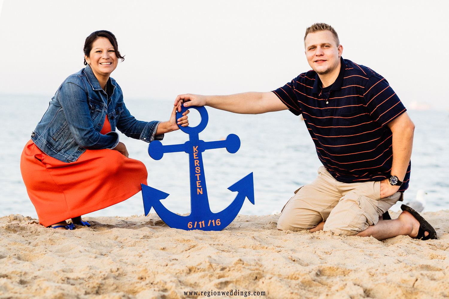 An engaged couple displays their wedding date on a boat anchor at North Avenue Beach in Chicago..