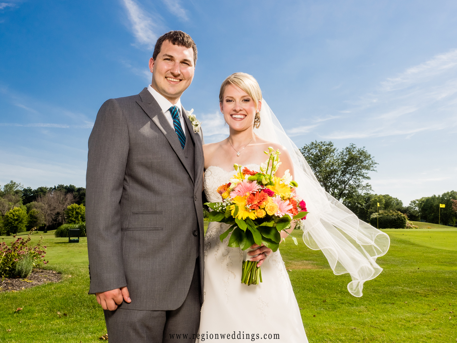 The bride and groom soak up the sun at Sand Creek Country Club.