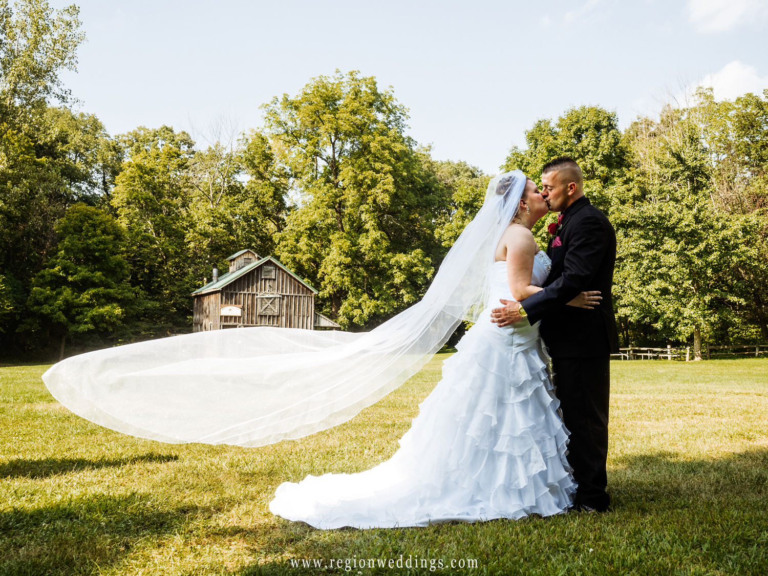 The bride's long veil flies in the air at Deep River County Park.