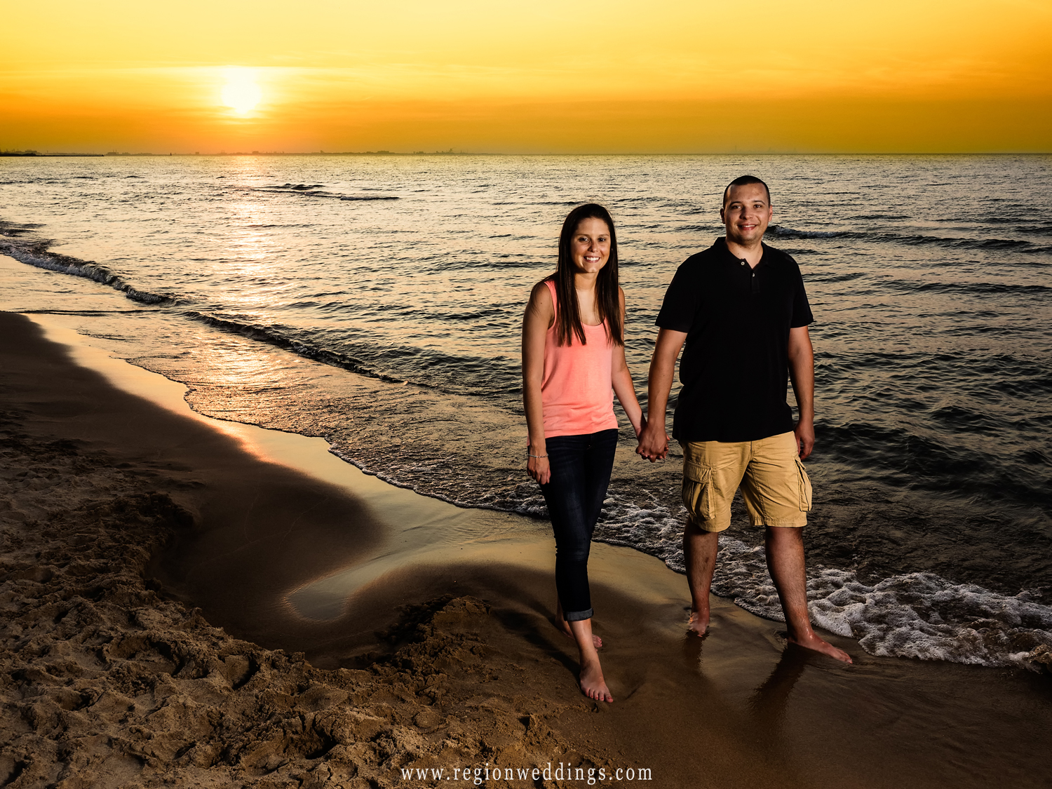 A young couple walks along Marquette Park Beach at sunset.