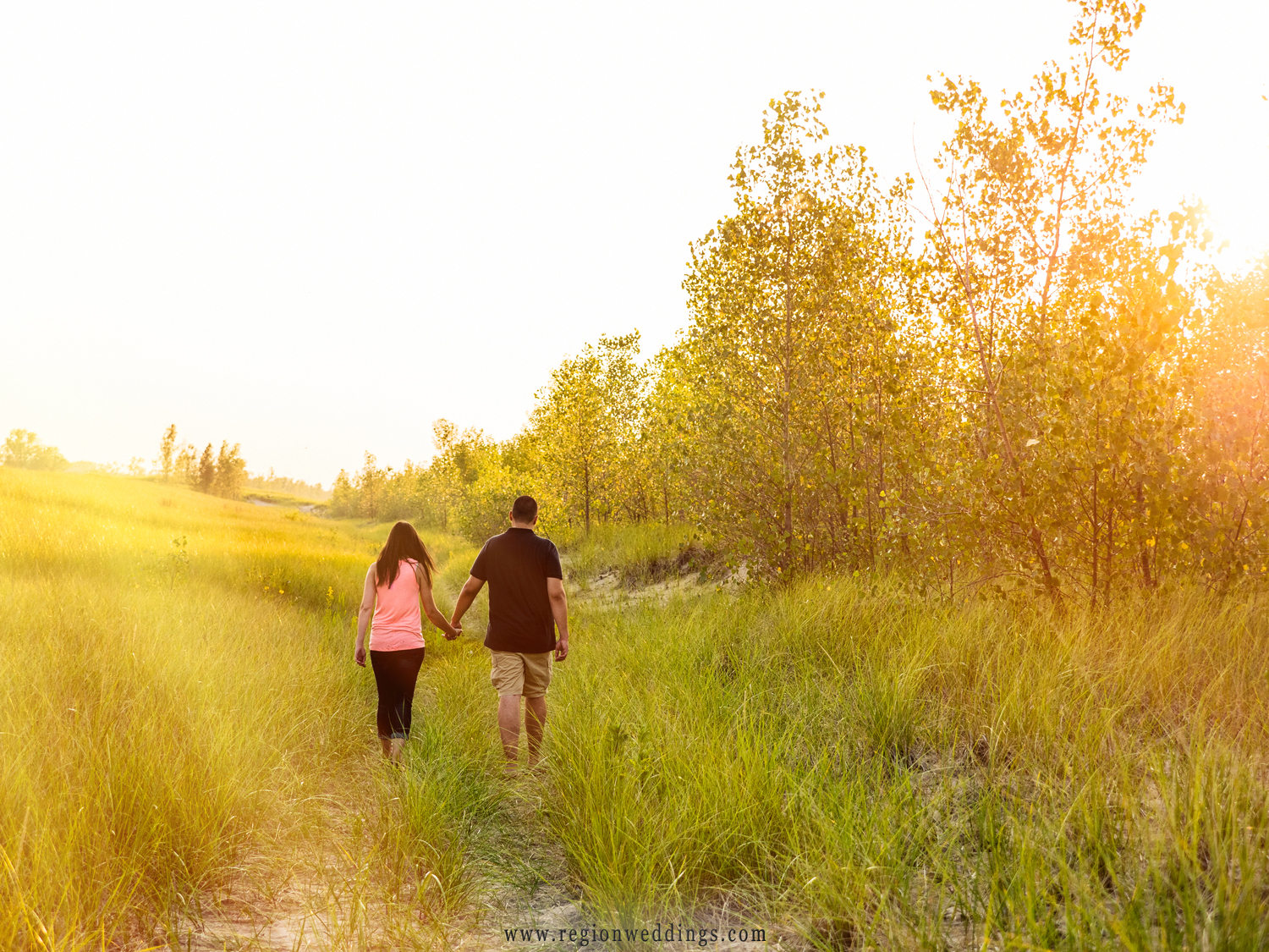 For their engagement photo, a couple strolls along a pathway at the Indiana Dunes.