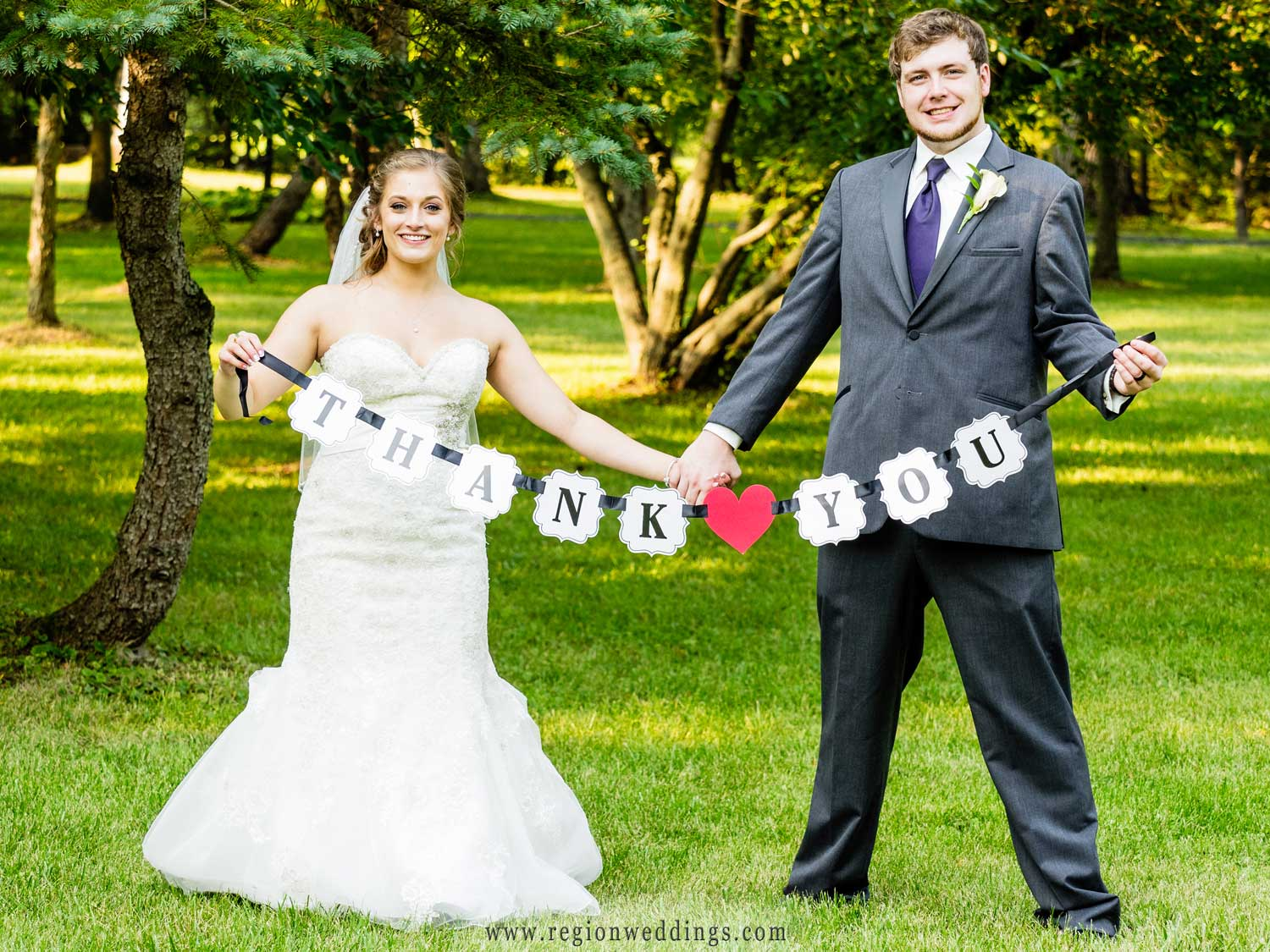 The bride and groom unfurl their Thank You banner.