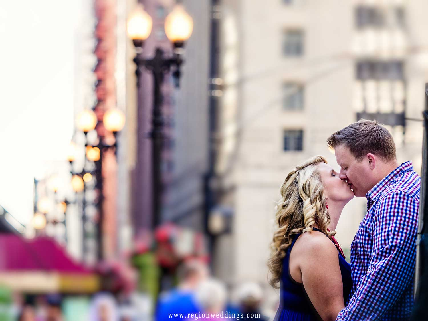A couple in love kisses beneath the street lamps of State Street.