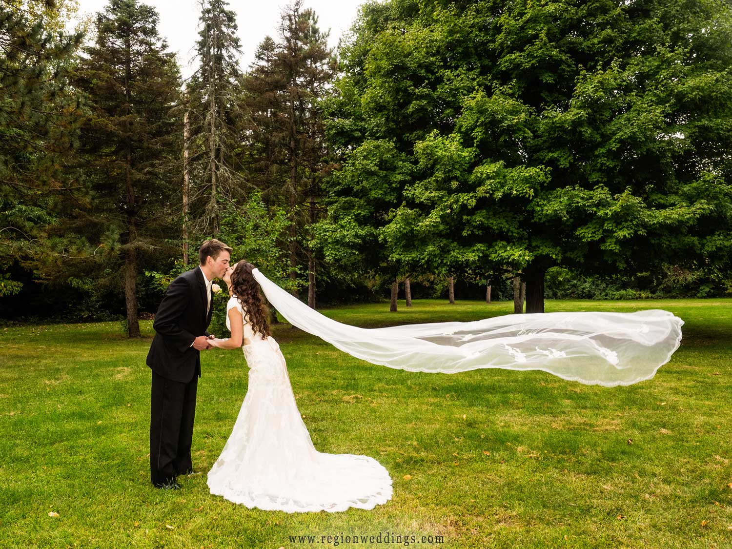 The veil floats on air as the bride and groom kiss.