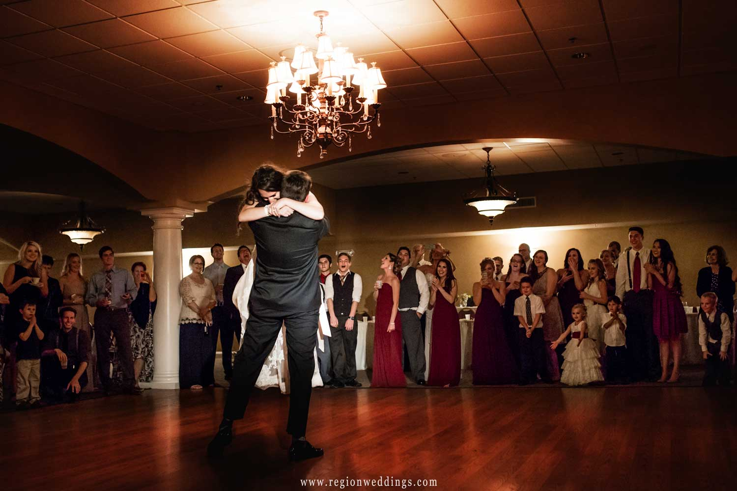 The groom lifts the bride into the air at Trinity Hall in Chesterton, Indiana.