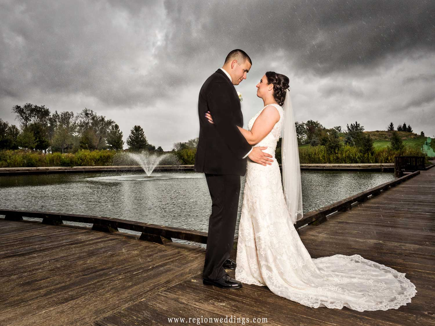 Rain falls upon the bride and groom at the Centennial Park fountain.