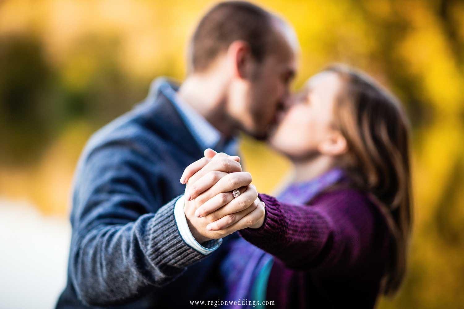 An engaged couple shows off her ring as they kiss in the background.