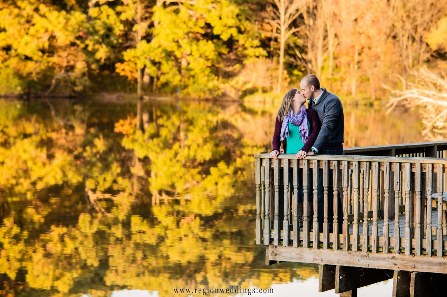 A young couple kisses on the edge of a pier with trees reflecting in the lake.