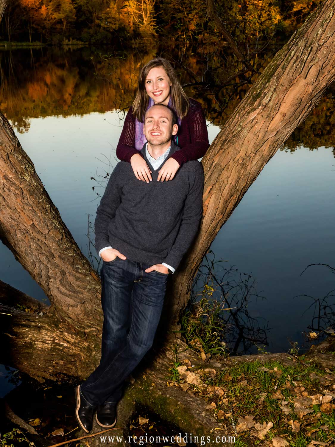 A portrait of an engaged couple perched alongside an old tree with Lemon Lake behind them.