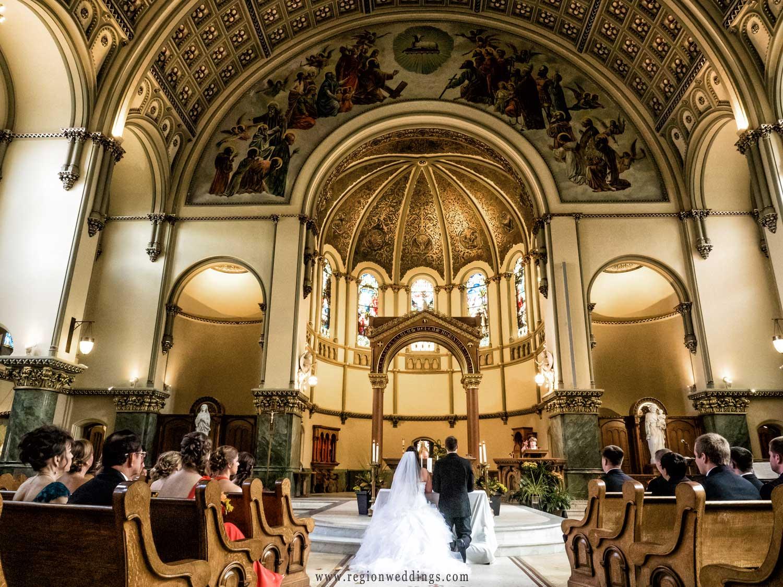 The bride and groom pray at Saint Josaphat Roman Catholic Church.