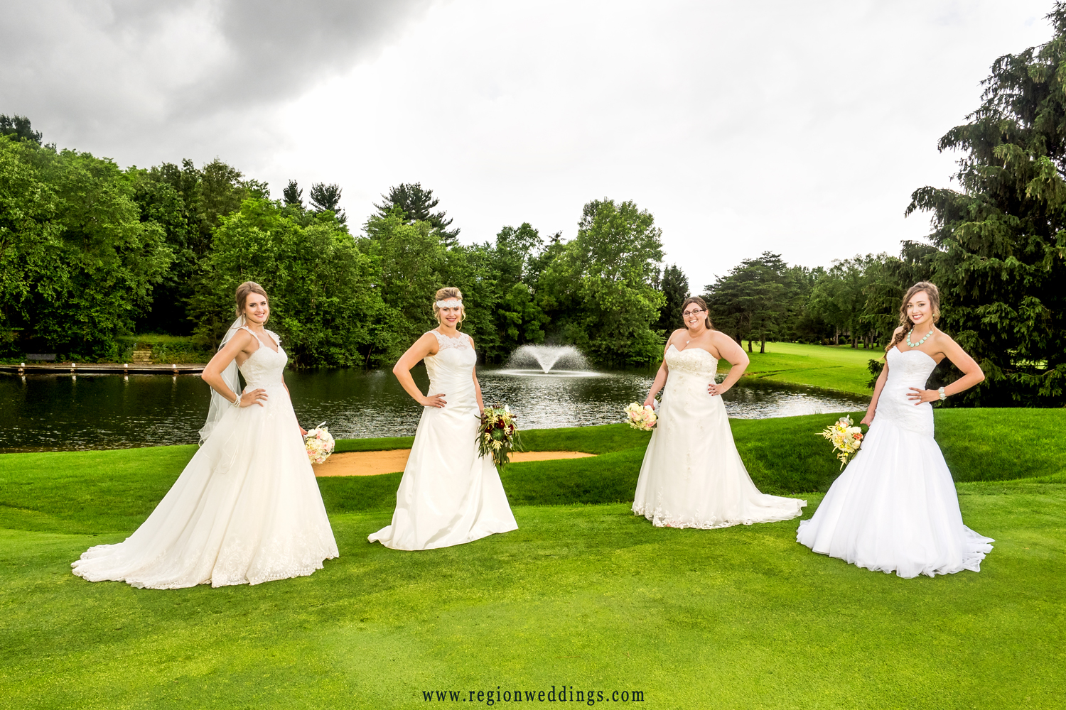 Four brides on the Sandy Pines Golf Course with the lake and fountain behind them.