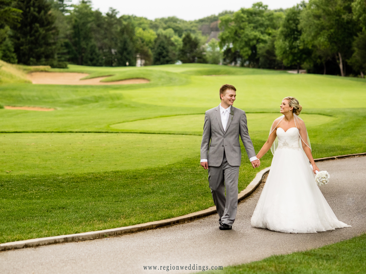 Bride and groom stroll the golf course at Sandy Pines in Demotte, Indiana.