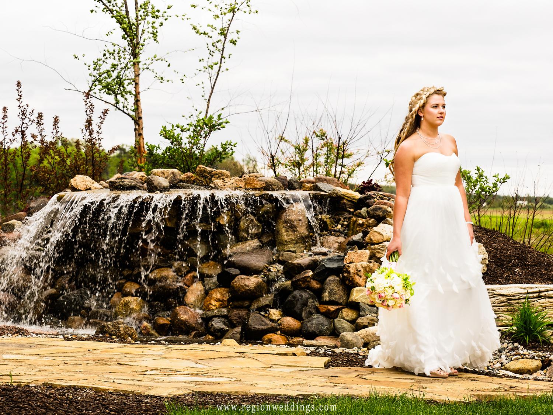Bride walks along the waterfall at The Restaurant At Fair Oaks Farms.