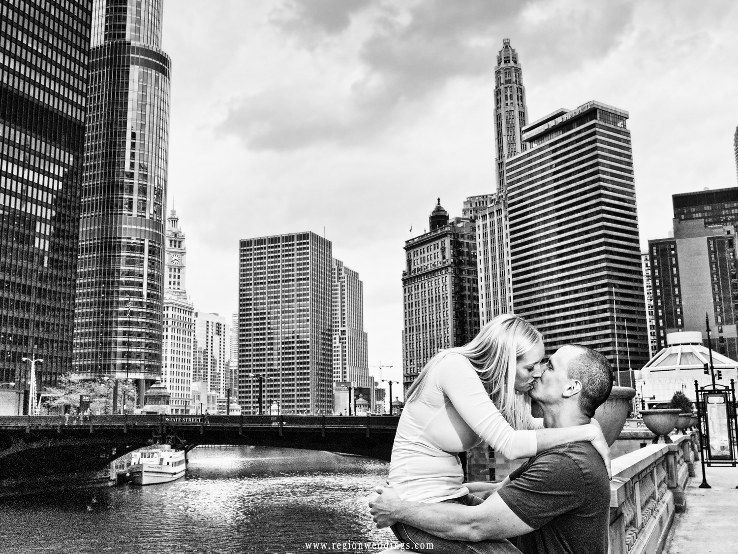A couple kisses on the rail at the Chicago River with skyscrapers behind them.