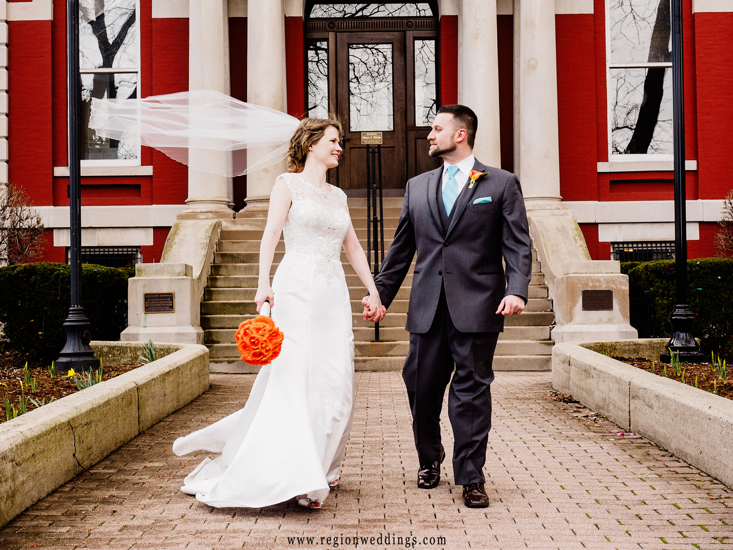 The bride's veil flies in the wind as the newlyweds take a stroll in downtown Crown Point.