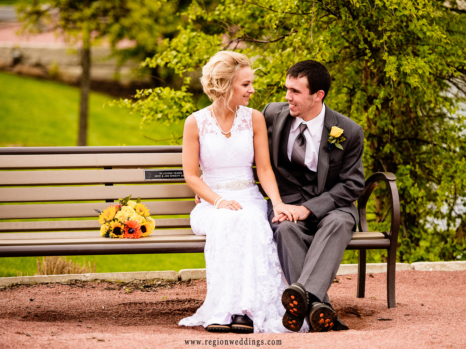Newlyweds cuddle up on a bench at Centennial Park in Munster, Indiana