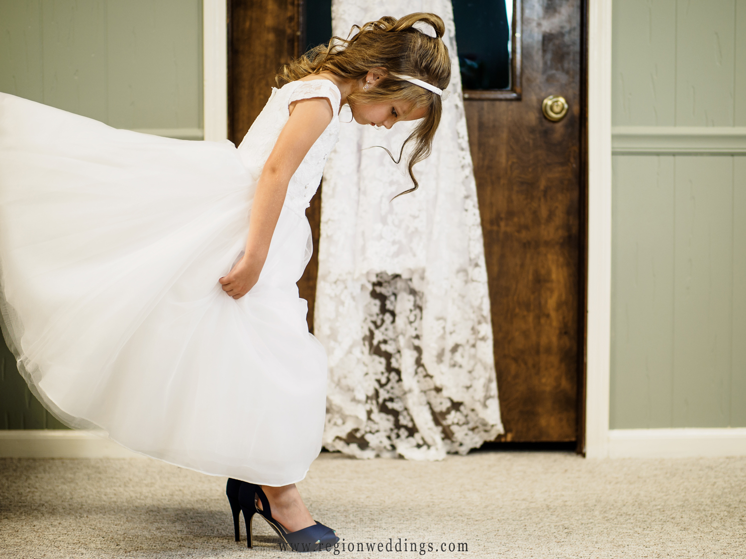 Flower girl steps into the bride's wedding shoes.