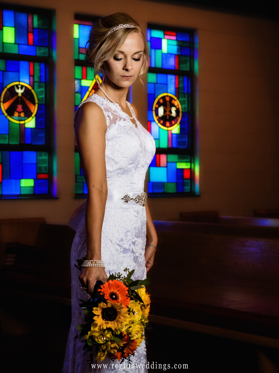 The bride looks down at her bouquet with stained glass windows behind her.