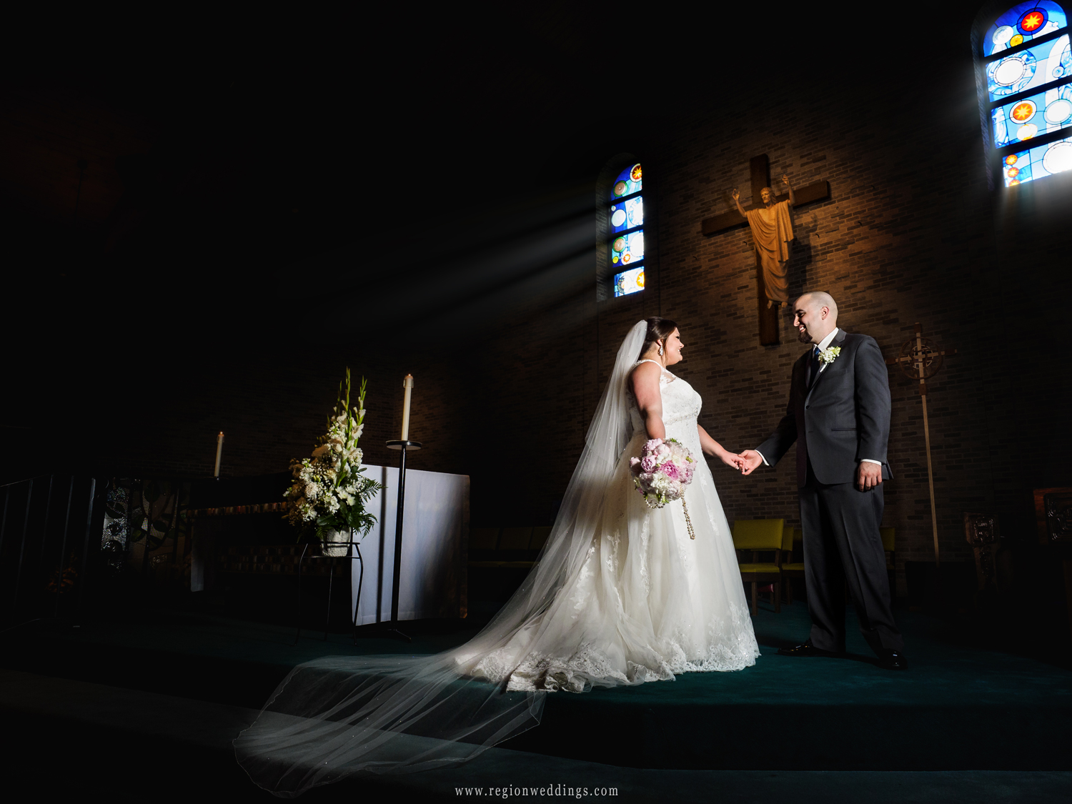 Bride and groom on the altar as light streams in through stained glass windows.