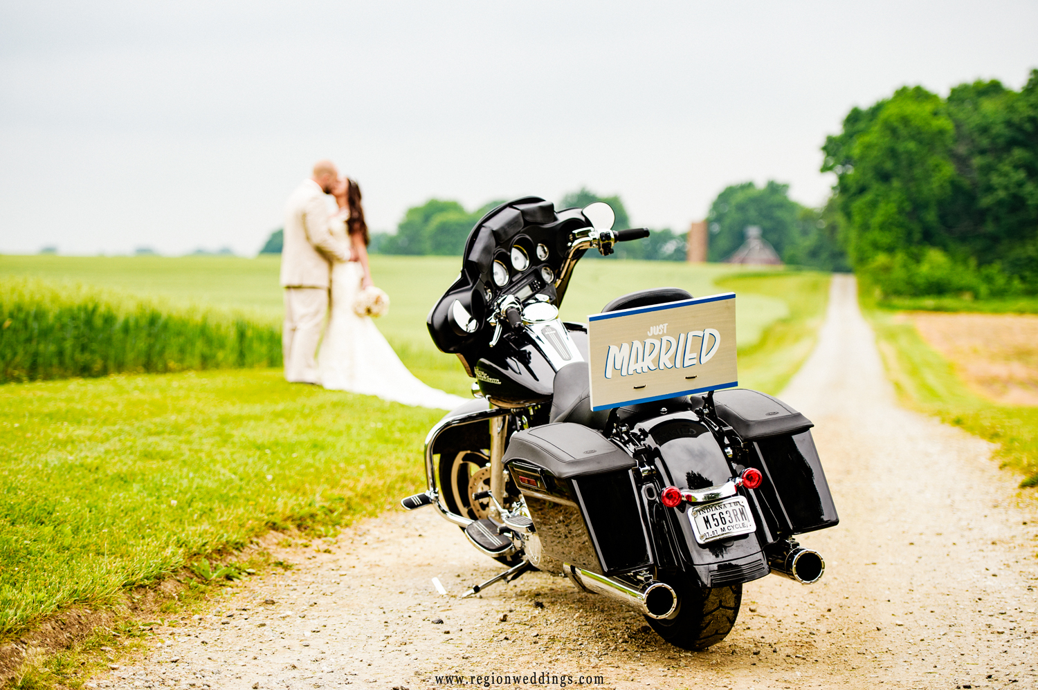 Just married sign on the back of a Harley Davidson as the bride and groom kiss in the background.