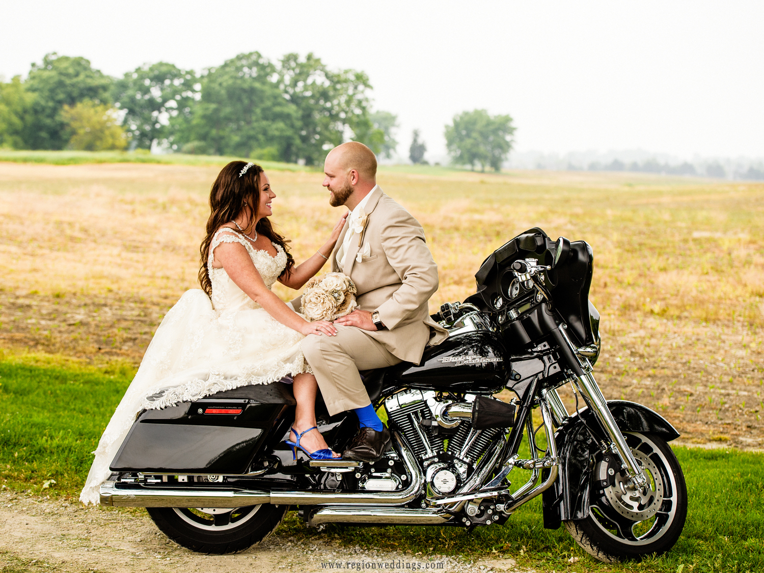 The bride and groom face each other on their Harley Davidson bike with farmland as their backdrop.