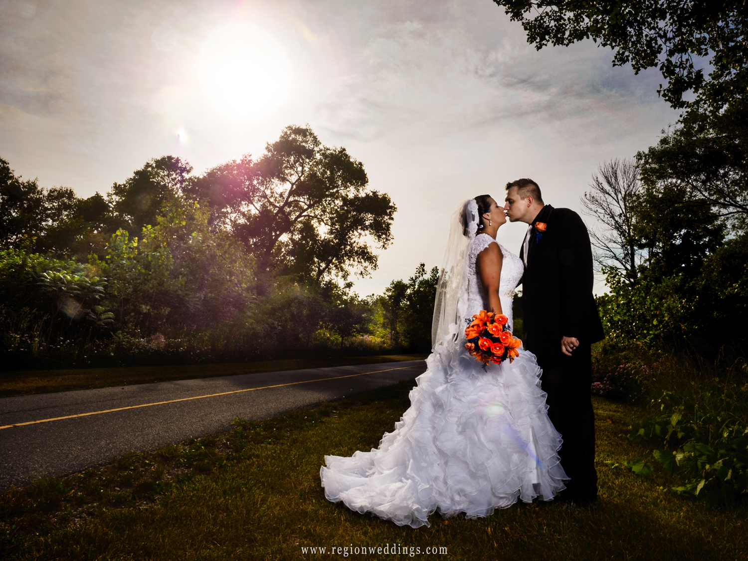 The bride and groom kiss with a sun burst in the sky above them.