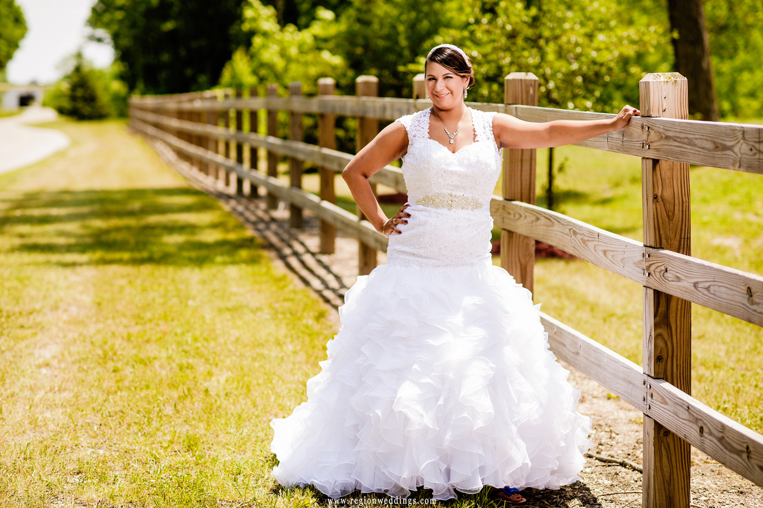 The bride leans against a rustic fence during her June wedding in Schererville.