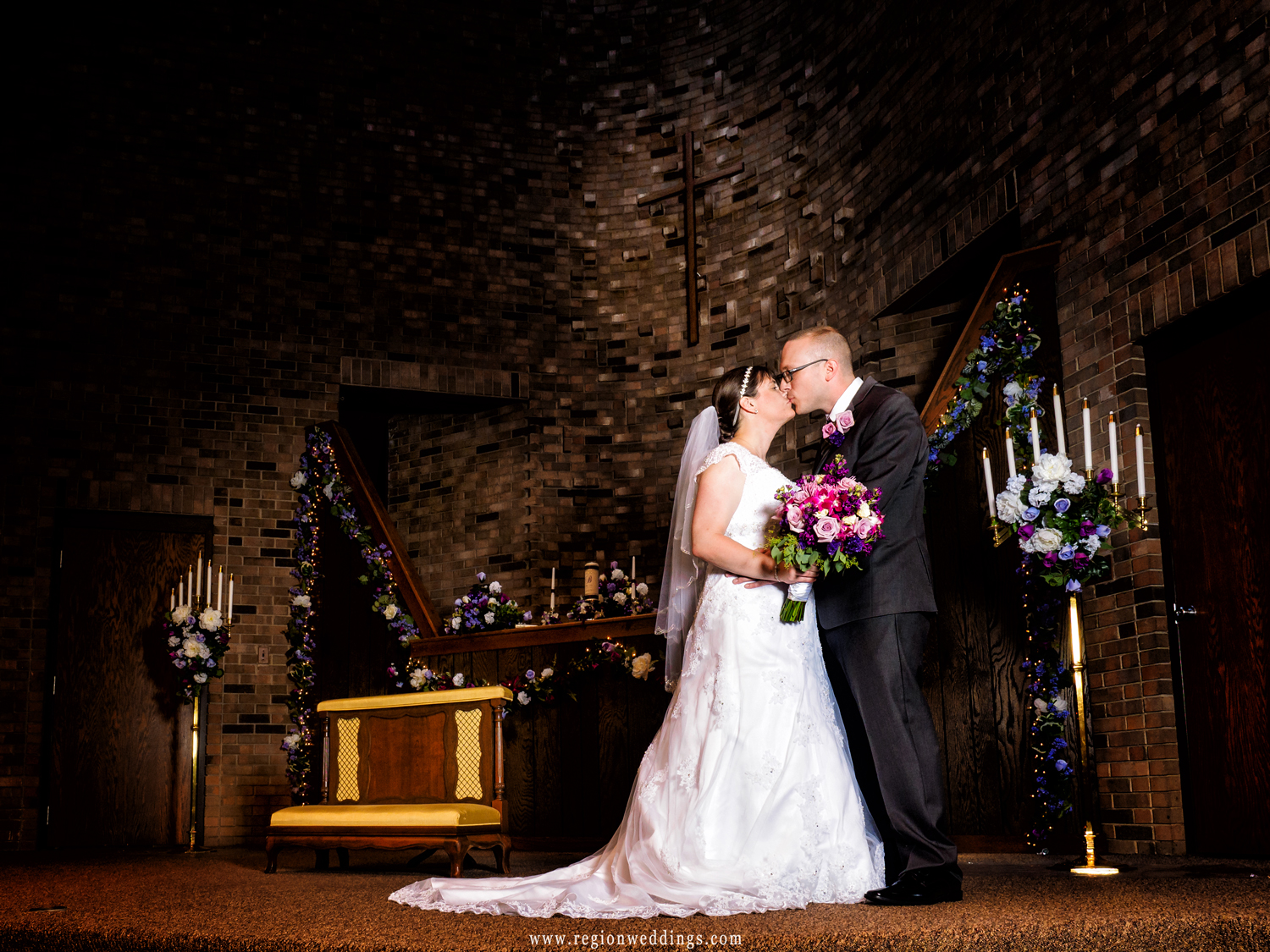 The bride and groom kiss on the altar at First Christian Church in Crown Point.