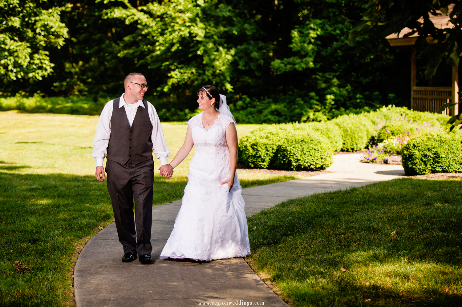 The bride and groom take a stroll in a Crown Point park with a gazebo in the background.