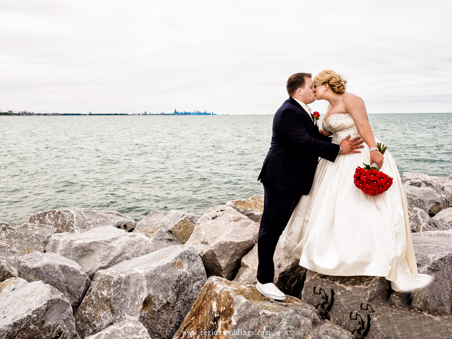 The bride and groom share a kiss on the rocks of the shoreline at Whiting Lakefront Park.
