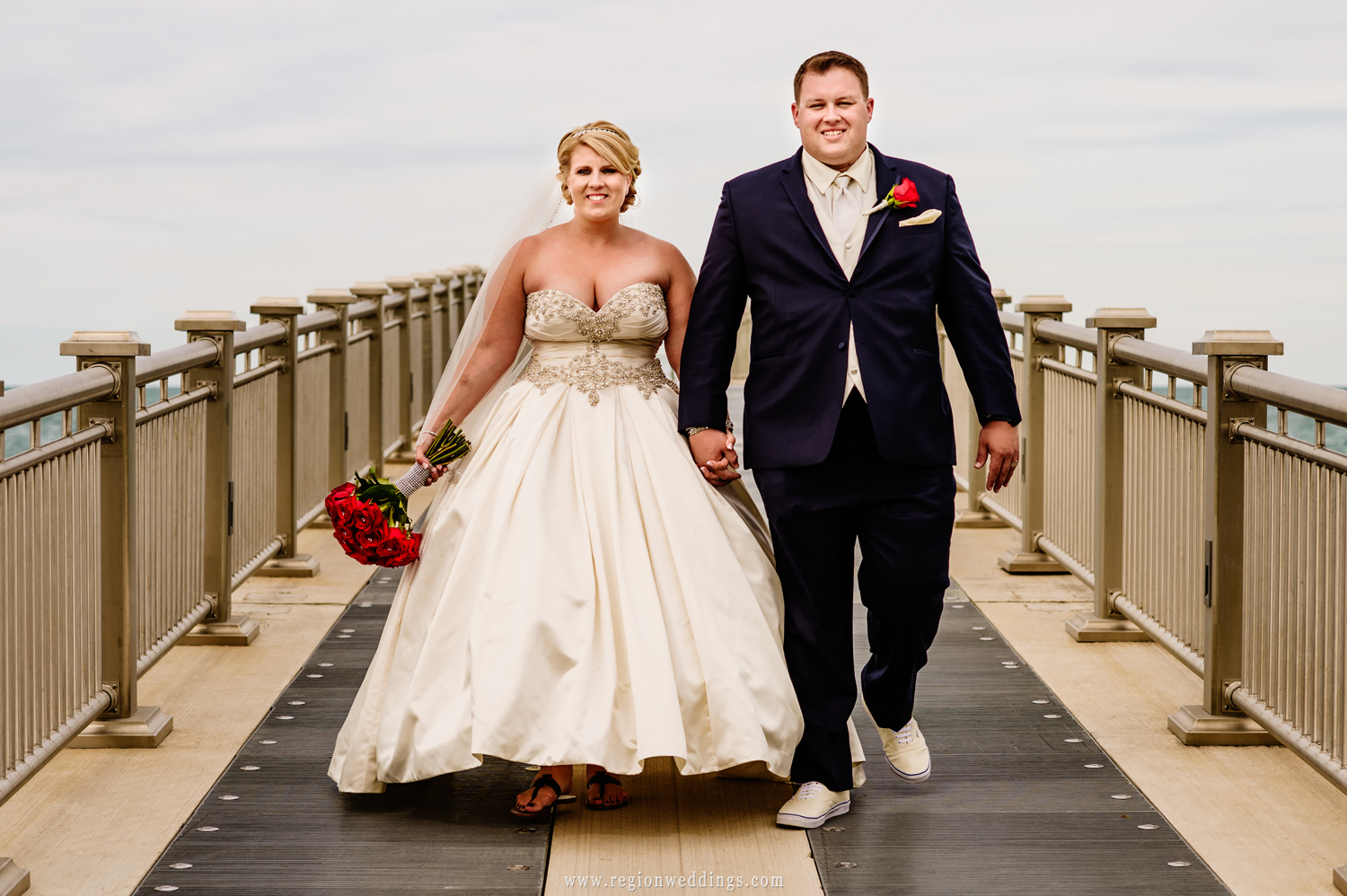 The bride and groom take a walk along the pier at Whiting Lakefront Park.