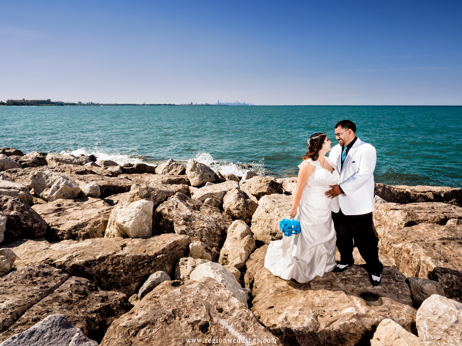 Bride and groom on the shore of Lake Michigan with Chicago in the background.