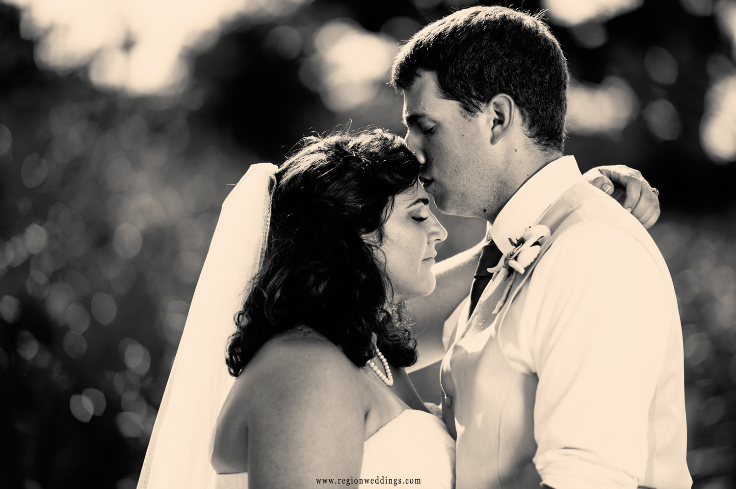 The bride and groom embrace on the beach after their summer wedding ceremony.