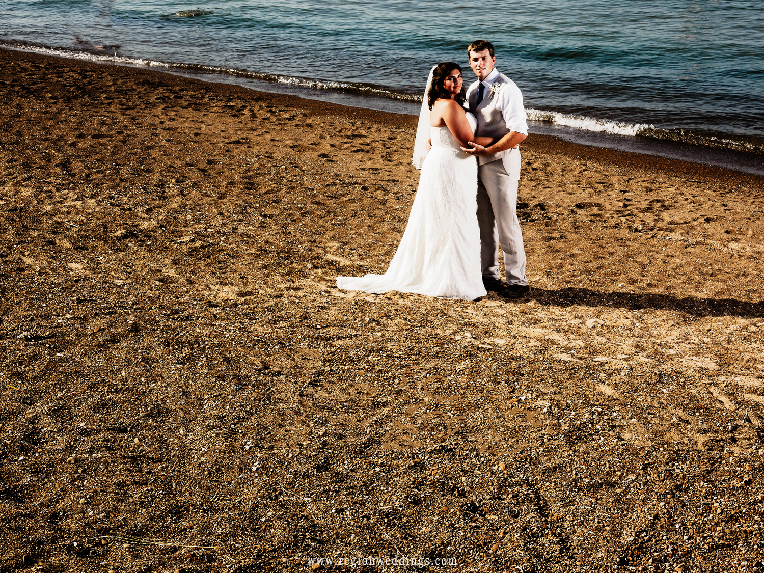 The bride and groom on a Lake Michigan beach as waves roll onto the shore.
