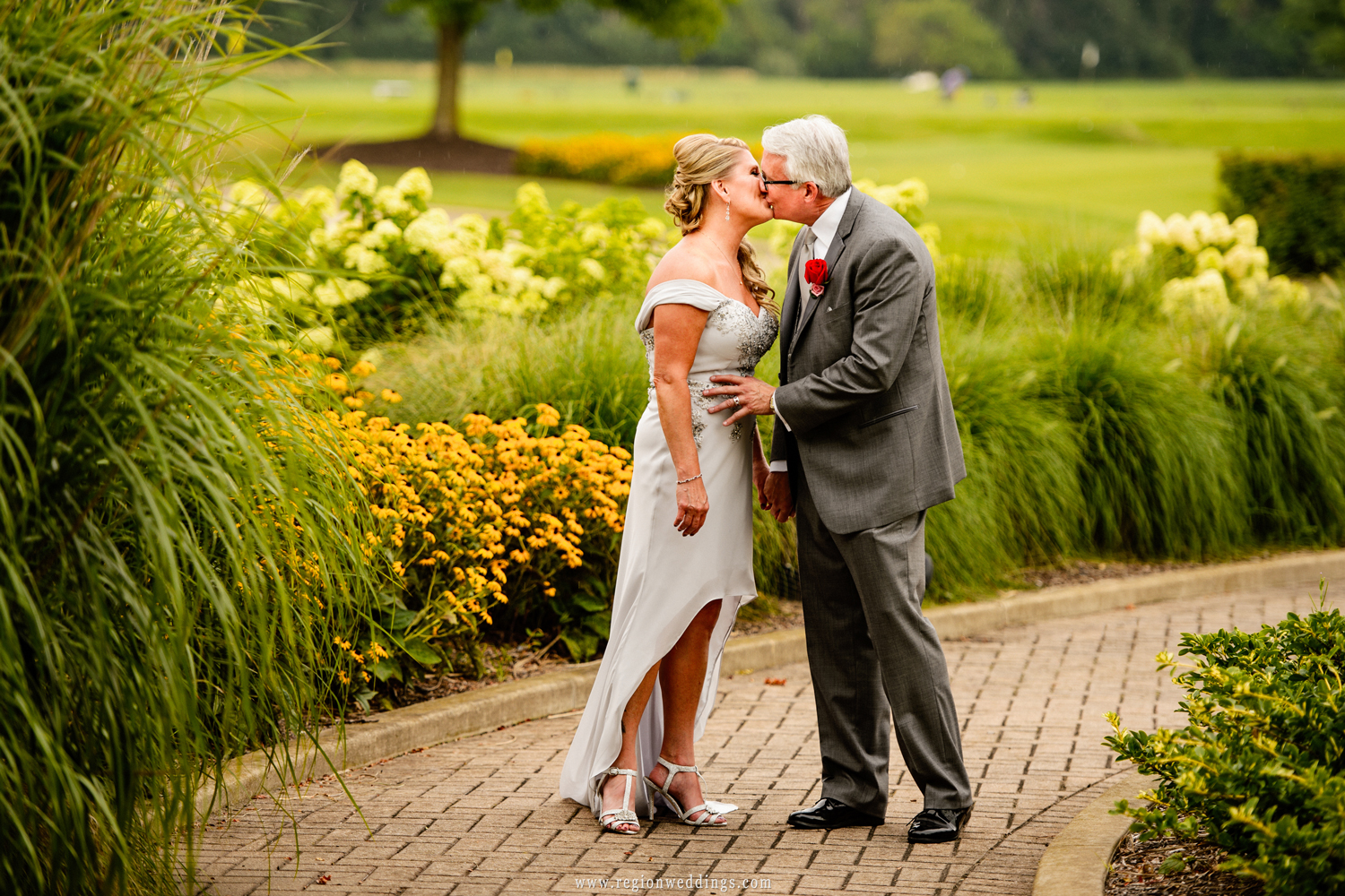 A newly married couple kisses in the garden of Sand Creek Country Club.