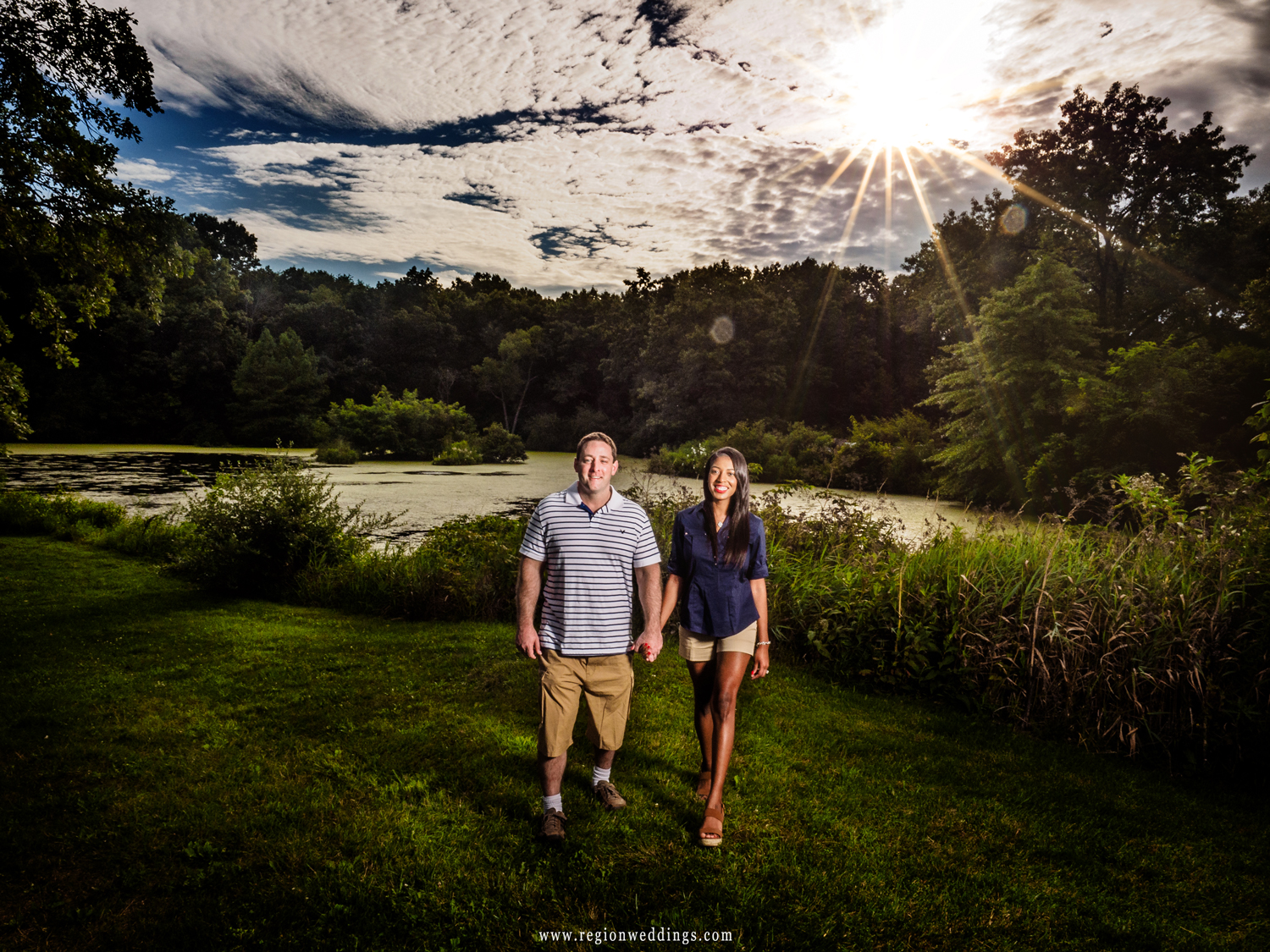 A cute couple takes a stroll besides the lake at Taltree Arboretum with a big ball of sun in the sky.