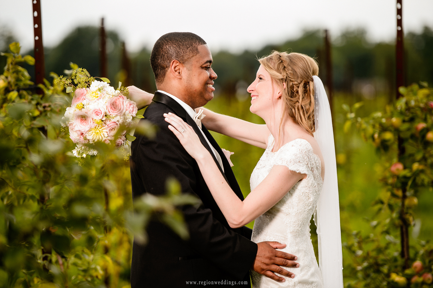 The bride and groom embrace deep within the apple orchards at County Line Orchard.