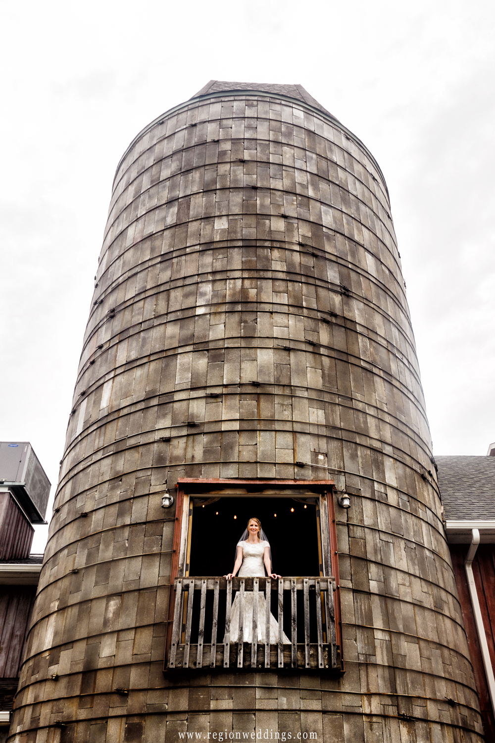 The bride stands on the balcony of the grain silo at County Line Orchard in Hobart, Indiana.