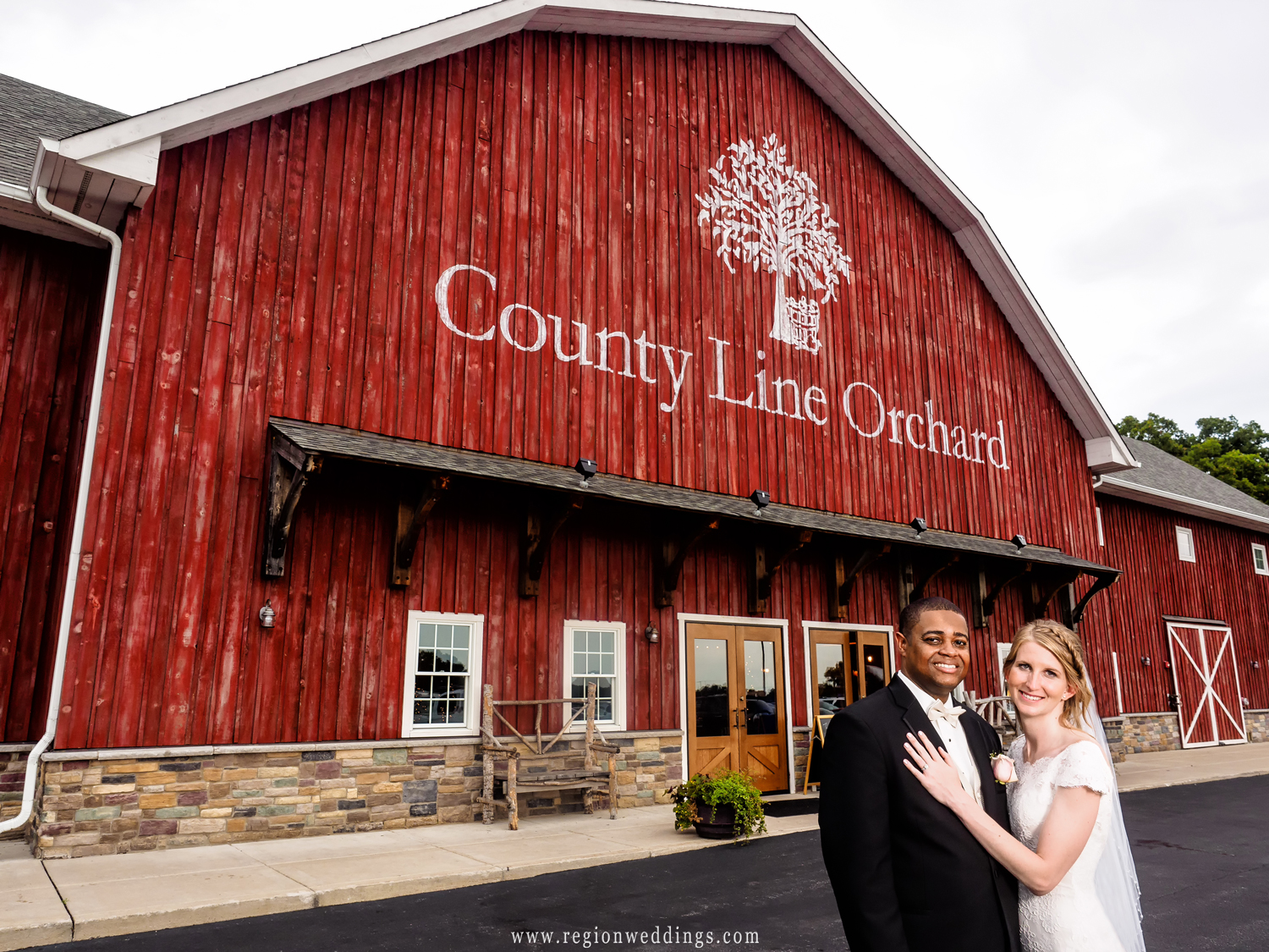 The bride and groom in front of the big red barn of County Line Orchard.