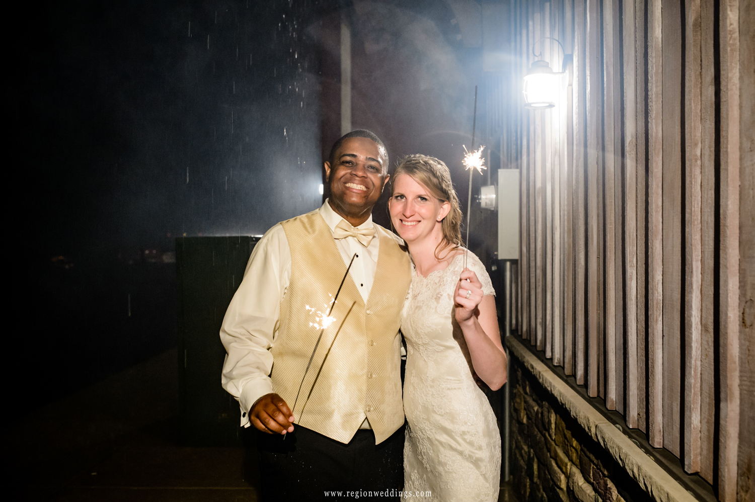 The bride and groom pose with sparklers at their wedding reception.