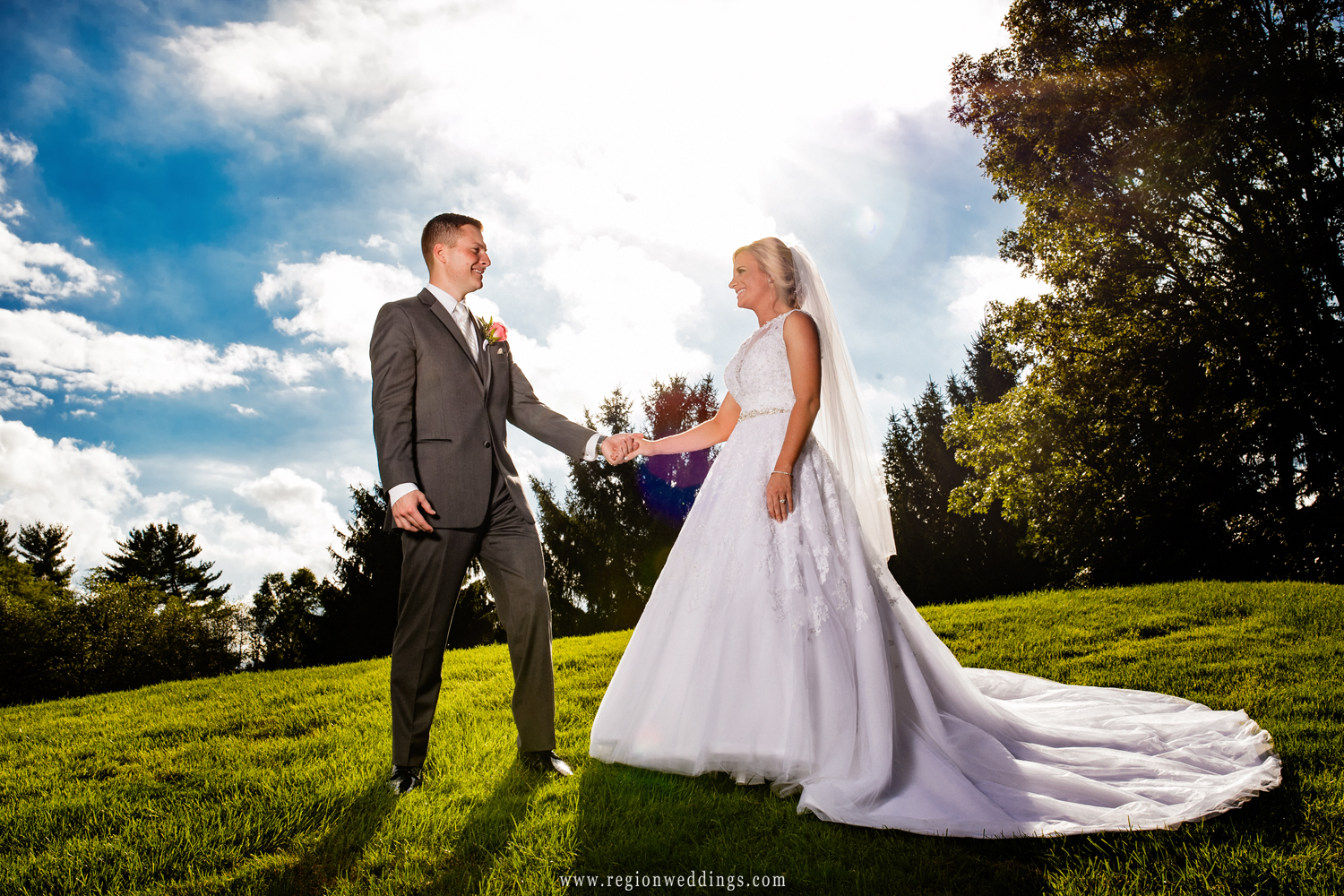 Bride and groom stand on a hill at Sandy Pines Golf Course