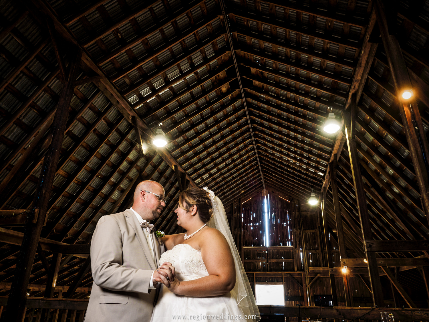 Bride and groom dance alone in the loft of Harold Wheeler Foundation Barn.