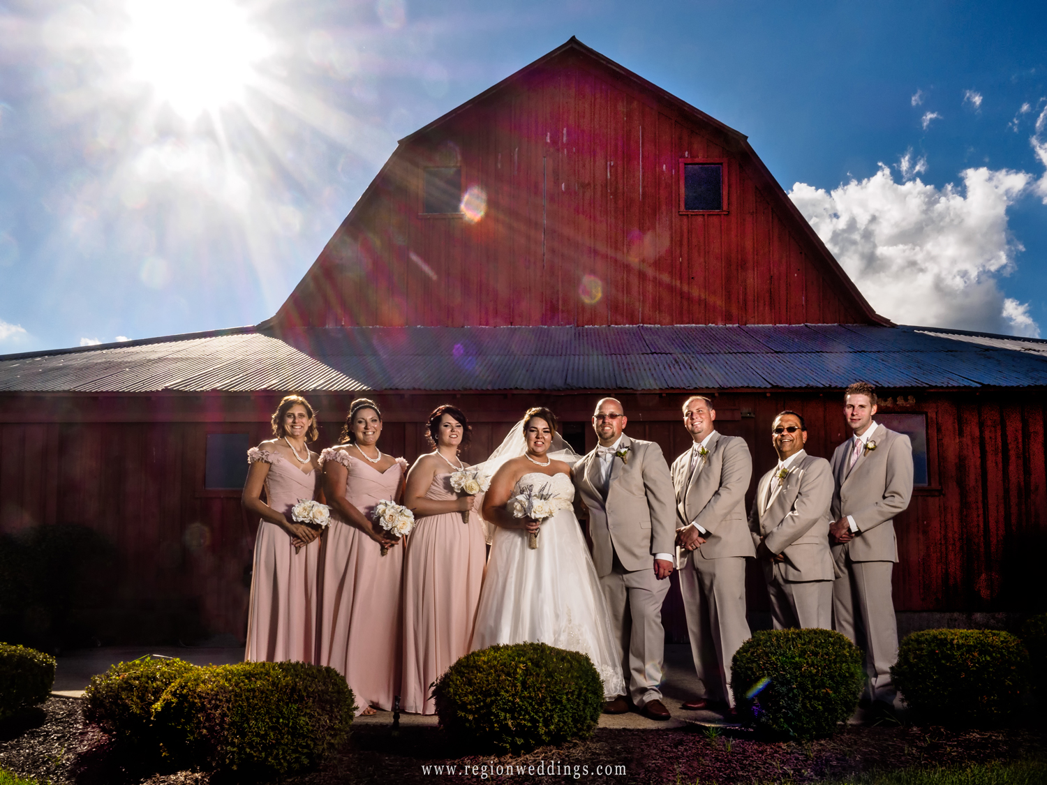 The wedding party at the back of the big red barn.
