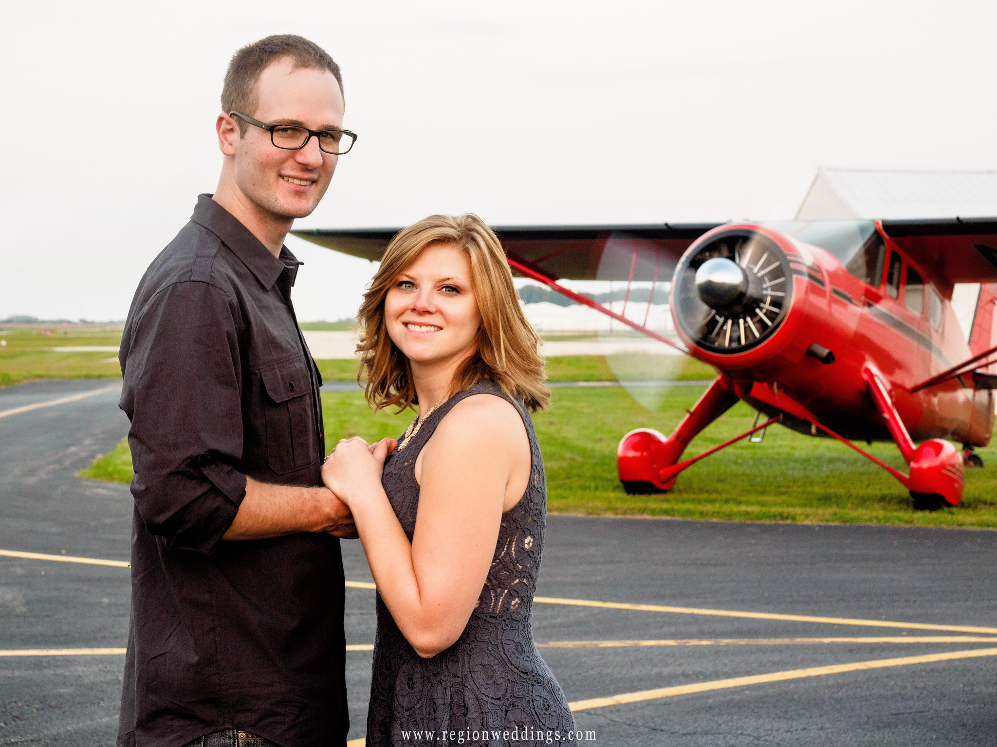 A young couple in front of a vintage airplane with it's propellors spinning.