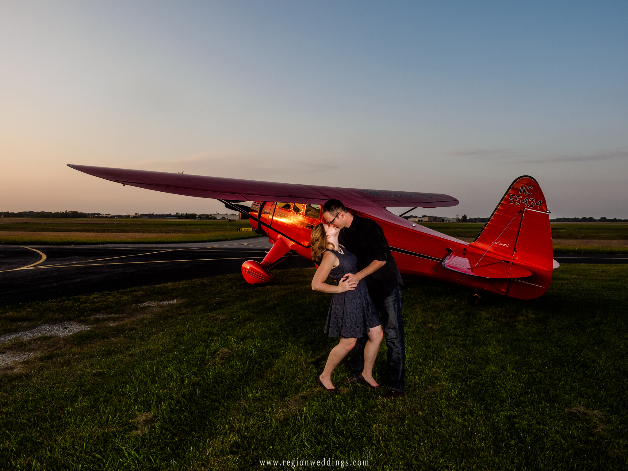 The groom to be dips his bride to be on the tarmac at Porter County Municipal Airport.