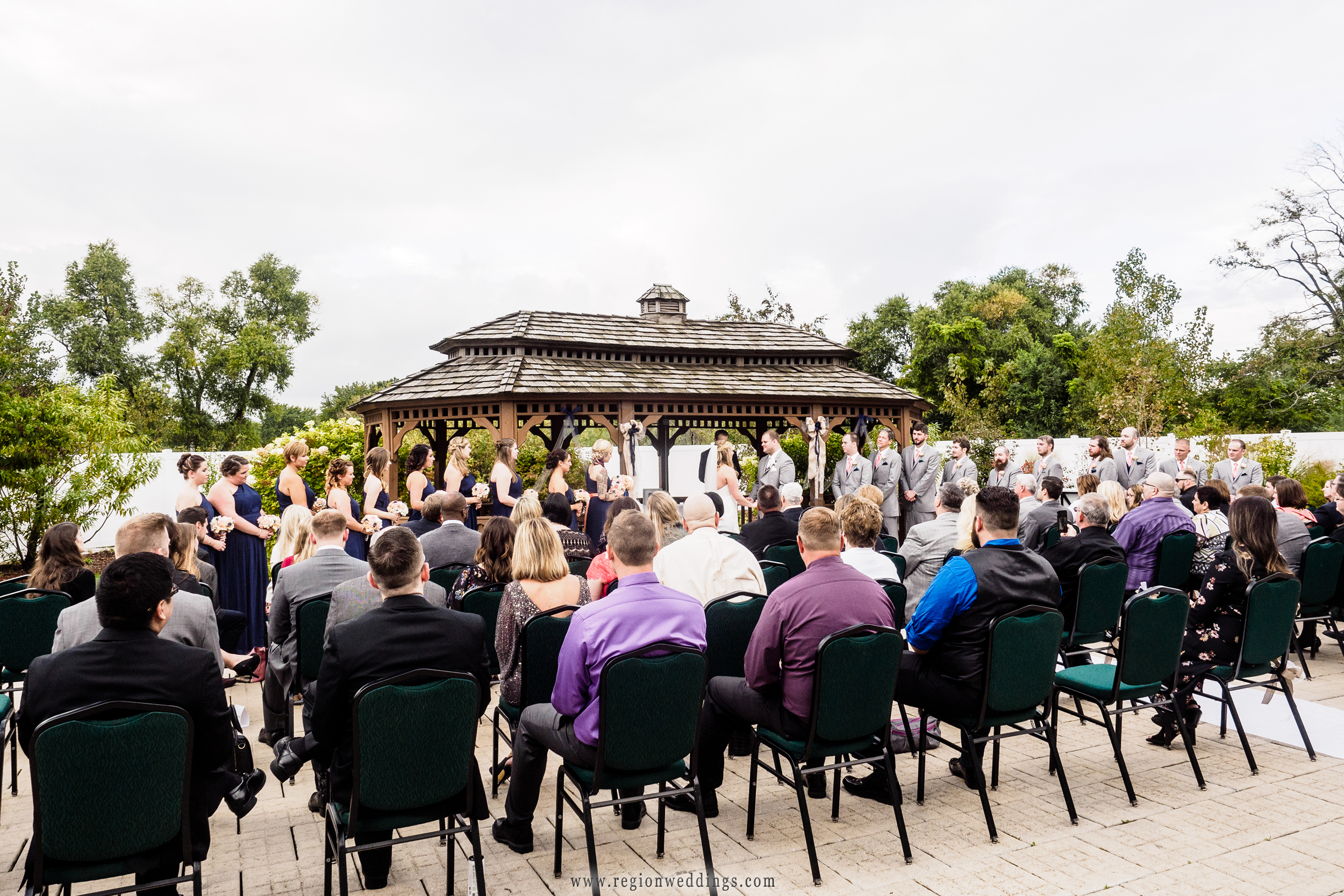 A large group of friends and family attend an outdoor wedding at The Patrician.